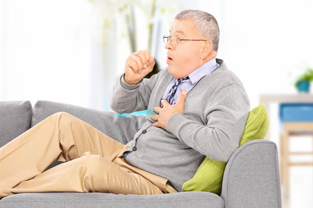 Anziano sul Divano con Tosse e Malattie Respiratorie